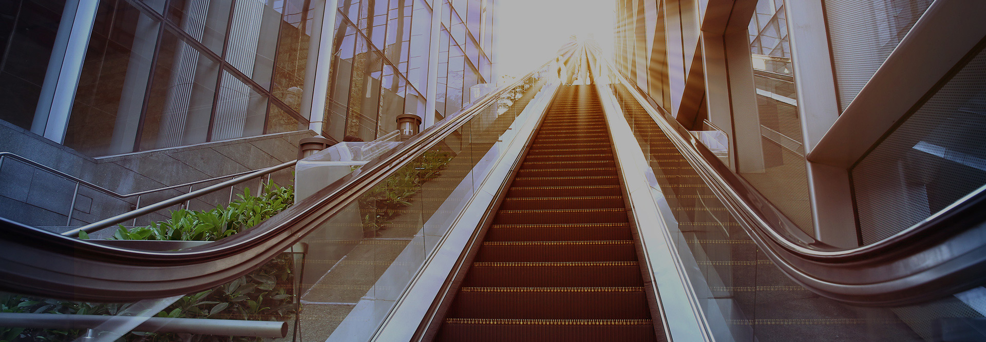 low-angle-shot-escalator-sun-flare-carouse-1920x667